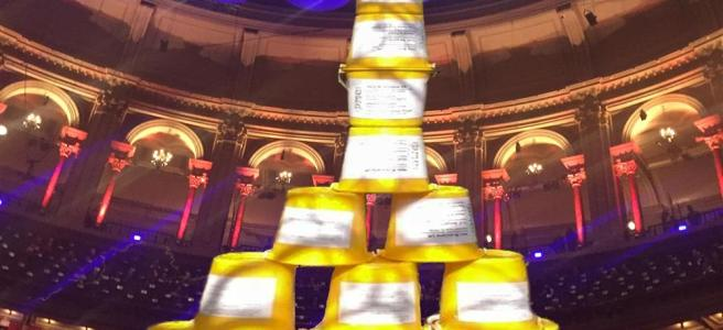 A pyramid of yellow buckets with Promenaders' Musical charities labels with a back drop of the auditorium of the Royal Albert Hall
